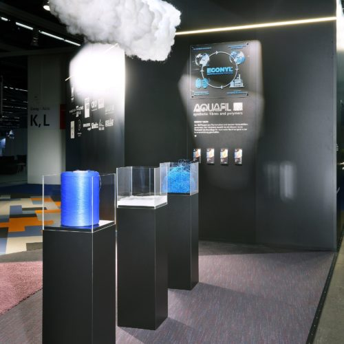 The wall in the booth with the description of the  ECONYL® REGENERATION SYSTEM by Aquafil.