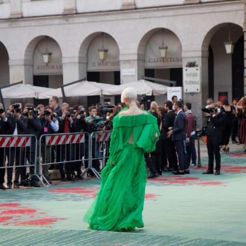 A top model with a green dress on the green carpet made by Aquafil at Milan Fashion Week top event at Piazza della Scala.
